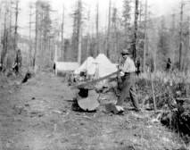 Image of Donaldson (bull cook) cutting wood. Zero Creek Planting Camp
