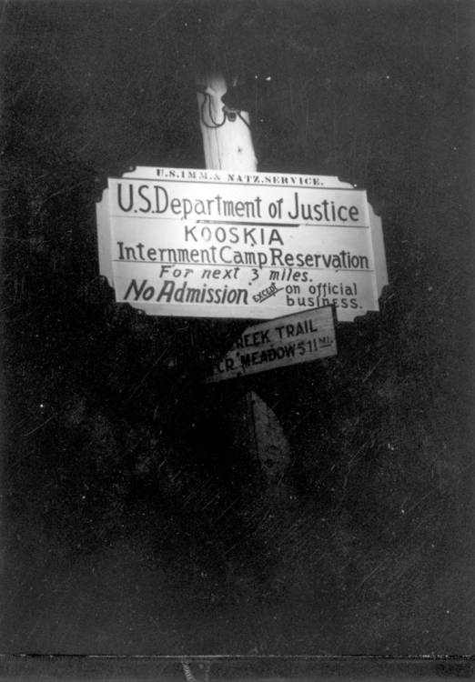 Image of sign at Kooskia Internment Camp reading, 'U.S. Department of Justice Kooskia Internment Camp Reservation for next 3 miles. No admission except on official business'. Photo taken from 12-3/4 x 15-1/4 Photograph album of the Kooskia Japanese Internment Camp.